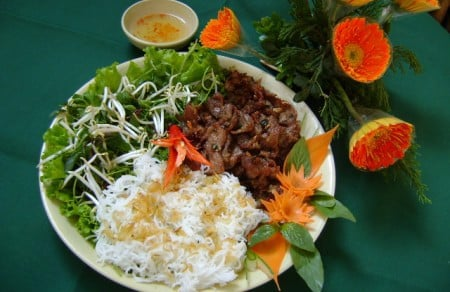 Grilled delicacies pork served with rice noodle and fresh herb vegetables
