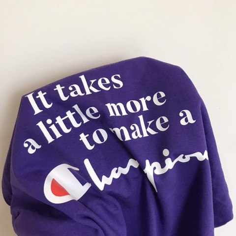 P100003 CHAMPION AUTHENTIC IT TAKES A LITTLE MORE TO MAKE A CHAMPION TEE