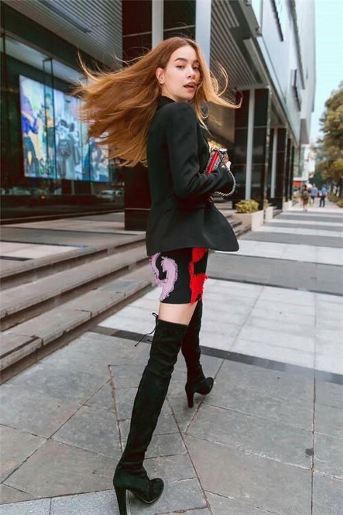 """Giọng ca Gửi người yêu cũ mix đồ khá linh hoạt và sáng tạo với boots cổ cao. Tuy nhiên có thể thấy cô ưa chuộng nhất """"công thức"""" boots cao cổ kết hợp váy ngắn suông hoặc bó sát, mix áo măng tô dài bên ngoài."""